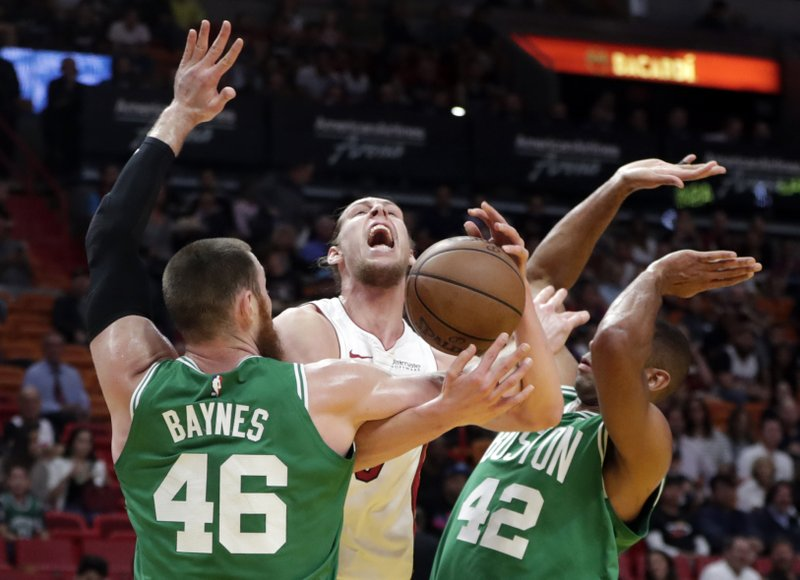 Miami Heat forward Kelly Olynyk, center, is fouled by Boston Celtics center Aron Baynes (46), who defends along with center Al Horford (42) during the first half of an NBA basketball game Wednesday, April 3, 2019, in Miami. (AP Photo/Lynne Sladky)