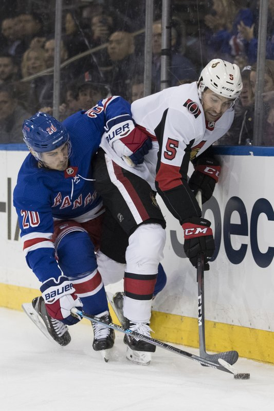 New York Rangers left wing Chris Kreider (20) and Ottawa Senators defenseman Cody Ceci (5) battle for the puck during the second period of an NHL hockey game, Wednesday, April 3, 2019, at Madison Square Garden in New York. (AP Photo/Mary Altaffer)