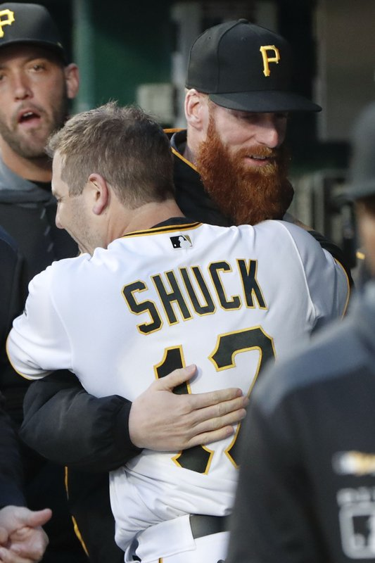Pittsburgh Pirates' JB Shuck (17) hugs Colin Moran in the dugout after he scored from first on a triple by Erik Gonzalez in the second inning of a baseball game against the St. (AP Photo/Keith Srakocic)