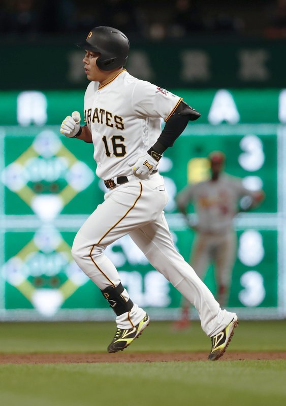 Pittsburgh Pirates' Jung Ho Kang (16) rounds the bases in front of St. Louis Cardinals right fielder Dexter Fowler after hitting a solo home run in the third inning of a baseball game, Wednesday, April 3, 2019, in Pittsburgh. (AP Photo/Keith Srakocic)