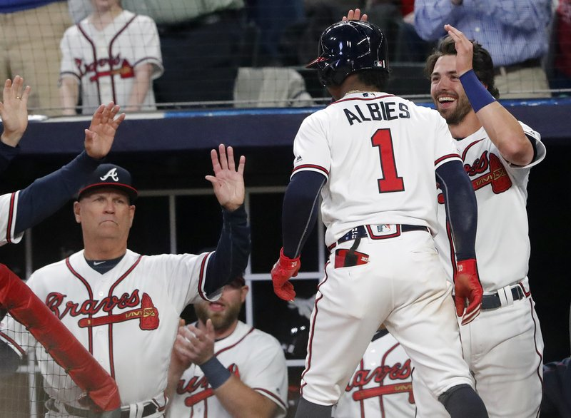 Atlanta Braves' Ozzie Albies (1) is greeted at the dugout by Dansby Swanson, right, and manager Brian Snitker after hitting a solo home run in the third inning of baseball game against the Chicago Cubs Wednesday, April 3, 2019, in Atlanta. (AP Photo/John Bazemore)