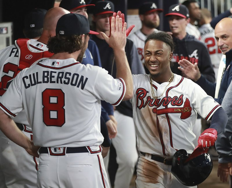 Atlanta Braves second baseman Ozzie Albies gets a high five from Charlie Culberson after hitting a solo home run during the third inning of a baseball game against the Chicago Cubs, Wednesday, April 3, 2019 in Atlanta. (Curtis Compton/Atlanta Journal-Constitution via AP)