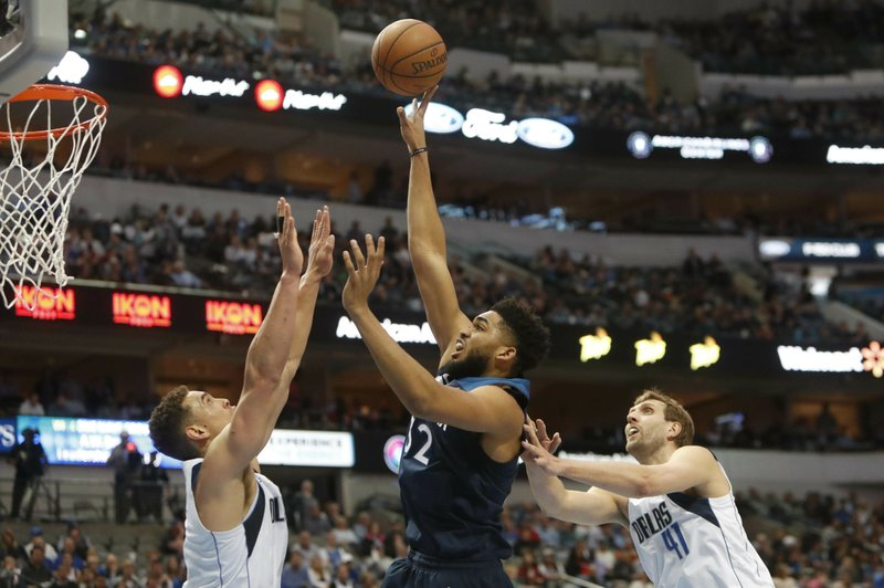 Minnesota Timberwolves center Karl-Anthony Towns (32) shoots against Dallas Mavericks defenders Dwight Powell (7) and Dirk Nowitzki (41) during the first half of an NBA basketball game in Dallas, Wednesday, April 3, 2019. (AP Photo/LM Otero)