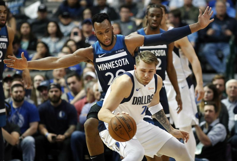 Dallas Mavericks forward Luka Doncic (77) controls the ball next to Minnesota Timberwolves guard Josh Okogie (20) during the first half of an NBA basketball game in Dallas, Wednesday, April 3, 2019. (AP Photo/LM Otero)