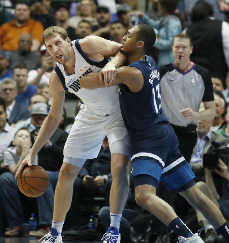 Dallas Mavericks forward Dirk Nowitzki (41) of Germany protects the ball from Minnesota Timberwolves guard Cameron Reynolds (13) during the first half of an NBA basketball game in Dallas, Wednesday, April 3, 2019. (AP Photo/LM Otero)