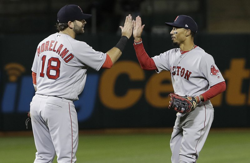 Boston Red Sox's Mitch Moreland (18) celebrates with Mookie Betts after the Red Sox defeated the Oakland Athletics in a baseball game in Oakland, Calif. (AP Photo/Jeff Chiu)
