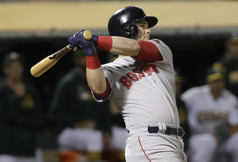 Boston Red Sox's Andrew Benintendi watches an RBI triple against the Oakland Athletics during the ninth inning of a baseball game in Oakland, Calif. (AP Photo/Jeff Chiu)