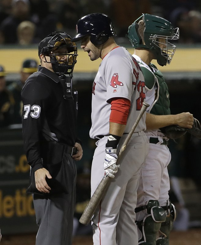 Boston Red Sox's J.D. Martinez, center, argues with umpire Tripp Gibson, left, after striking out during the eighth inning against the Oakland Athletics in a baseball game in Oakland, Calif. (AP Photo/Jeff Chiu)