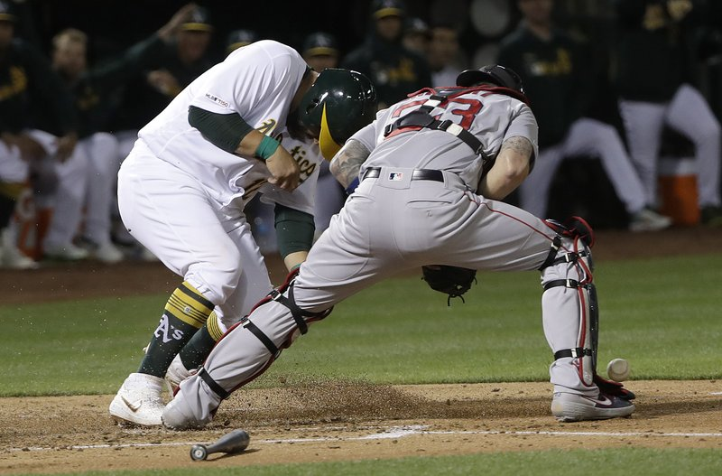 Oakland Athletics' Kendrys Morales, left, scores a run past Boston Red Sox catcher Blake Swihart during the second inning of a baseball game in Oakland, Calif. (AP Photo/Jeff Chiu)