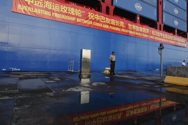 In this Dec. 3, 2018, photo, a Panama Canal guard stands at attention in front of a Chinese container ship docked at the Panama Canal's Cocoli Locks in Panama City, during an official visit by China's President Xi Jinping and first lady Peng Liyuan. (AP Photo/Arnulfo Franco)