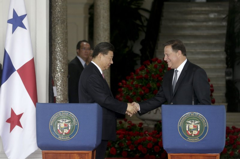 FILE - In this Dec. 3, 2018, file photo, Chinese President Xi Jinping, left, and Panama's President Juan Carlos Varela shakes hands after reading a statement and meeting at the presidential palace in Panama City. (AP Photo/Arnulfo Franco, File)