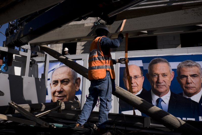 Israel Electric Corporation employee works next to election campaign billboards showing Israeli Prime Minister and head of the Likud party Benjamin Netanyahu, left, alongside the Blue and White party leaders, from left to right, Moshe Yaalon, Benny Gantz, Yair Lapid, in Tel Aviv, Israel, Wednesday, April 3, 2019. (AP Photo/Oded Balilty)