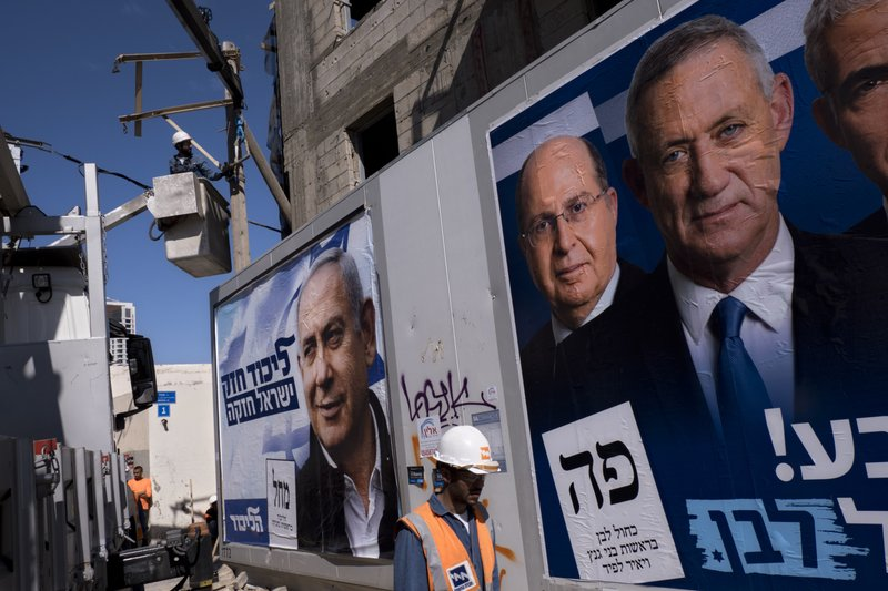 Israel Electric Corporation employees work next to election campaign billboards showing Israeli Prime Minister and head of the Likud party Benjamin Netanyahu, left, alongside the Blue and White party leaders, from left to right, Moshe Yaalon, Benny Gantz, in Tel Aviv, Israel, Wednesday, April 3, 2019. (AP Photo/Oded Balilty)