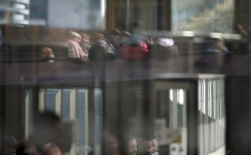 People are reflected in the glass as they wait outside EU headquarters in the EU district of Brussels, Thursday, April 4, 2019. (AP Photo/Virginia Mayo)