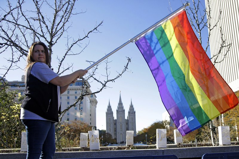 FILE - In this Nov. 14, 2015 file photo, Sandy Newcomb poses for a photograph with a rainbow flag as people gather for a mass resignation from The Church of Jesus Christ of Latter-day Saints in Salt Lake City. (AP Photo/Rick Bowmer, File)