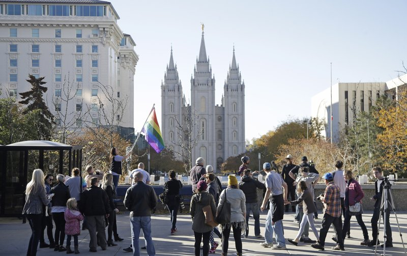 FILE - In this Nov. 14, 2015, file photo, people walk past the Salt Lake Temple after mailing resignation letters during a mass resignation from the Church of Jesus Christ of Latter-day Saints in Salt Lake City. (AP Photo/Rick Bowmer, File)