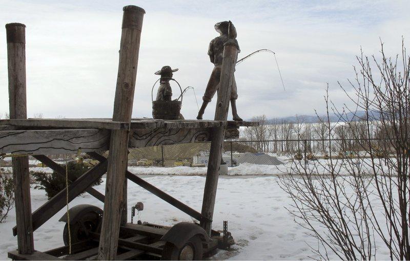 In this March 7, 2019 photo, shows a sculpture of a boy and girl fishing on the property that once housed Burlington College, and before that was an orphanage run by the Roman Catholic Diocese, in Burlington, Vt. (AP Photo/Wilson Ring)