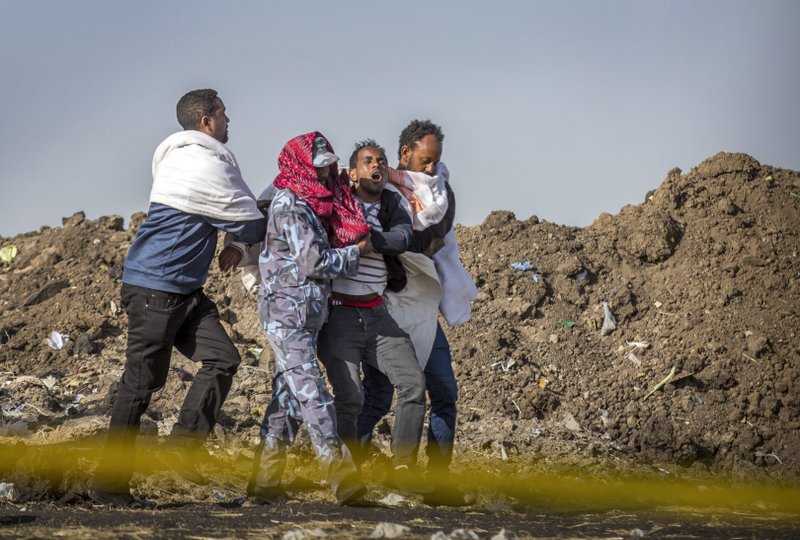 FILE - In this Wednesday March 13, 2019 file photo, a grieving relative who lost his wife in the plane crash is helped by a member of security forces and others near Bishoftu, in Ethiopia, at the scene where the Ethiopian Airlines jet crashed just after taking off from Addis Ababa on March 10, killing all 157 on board. (AP Photo/Mulugeta Ayene, File)