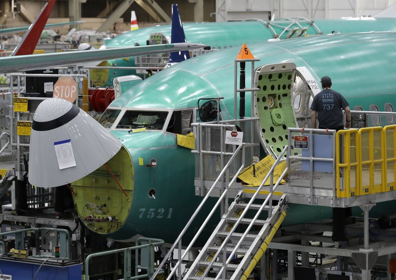 FILE - In this March 27, 2019, file photo, a worker enters a Boeing 737 MAX 8 airplane during a brief media tour of Boeing's 737 assembly facility in Renton, Wash. (AP Photo/Ted S. Warren, File)
