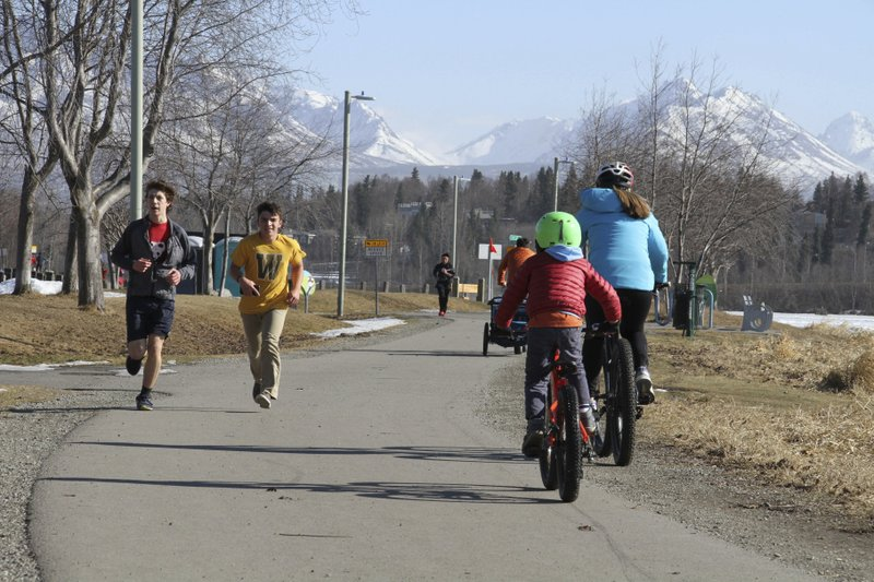 This April 3, 2019, photo shows people running and biking at Westchester Lagoon in Anchorage, Alaska, with the snow-covered Chugach Mountains in the distance. (AP Photo/Mark Thiessen)
