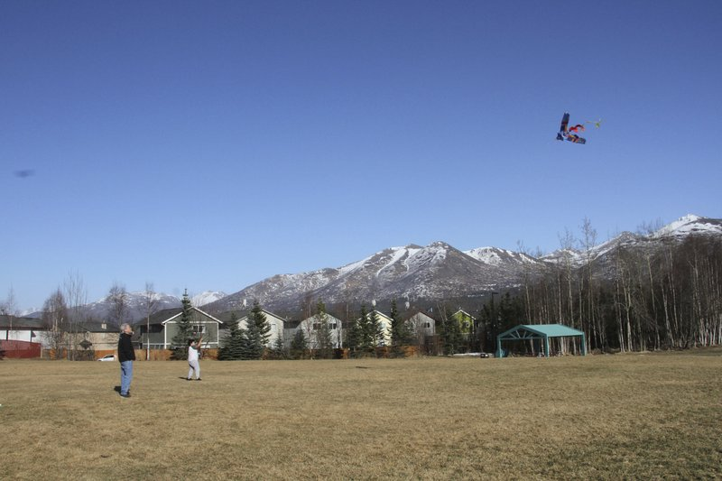 This March 3, 2019, photo shows 10-year-old Daniel Hansell, right, and his father, Jeff Hansell, flying a kite in a park in East Anchorage, Alaska, with the snow-covered Chugach Mountains in the background. (AP Photo/Mark Thiessen)