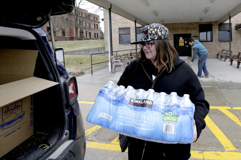 Leanne Achenbach of Bartlett, Iowa, carries donated water to her car at the Glenwood, Iowa, Resource Center Wednesday, April 3, 2019. (AP Photo/Nati Harnik)