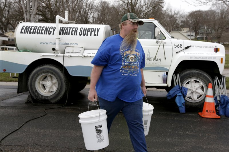 Adam Wilson of Glenwood, Iowa, walks away with buckets filled with water from Omaha's Municipal Utilities District's emergency water supply tanker, in Glenwood, Iowa, Wednesday, April 3, 2019. (AP Photo/Nati Harnik)