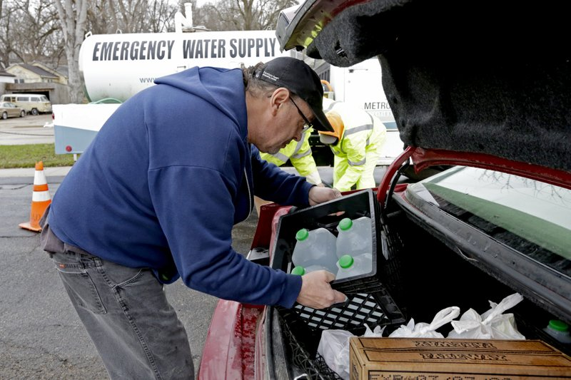 A resident loads jugs of water filled from Omaha's Municipal Utility District's emergency water supply tanker into the trunk of his car, in Glenwood, Iowa, into the trunk of his car into the trunk of his car Wednesday, April 3, 2019. (AP Photo/Nati Harnik)