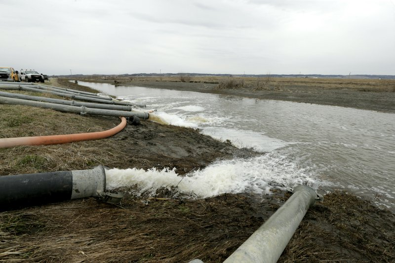 Flood waters from the fields and the town of Pacific Junction, Iowa, are pumped away to a drainage channel that leads back to the Missouri River Wednesday, April 3, 2019. (AP Photo/Nati Harnik)