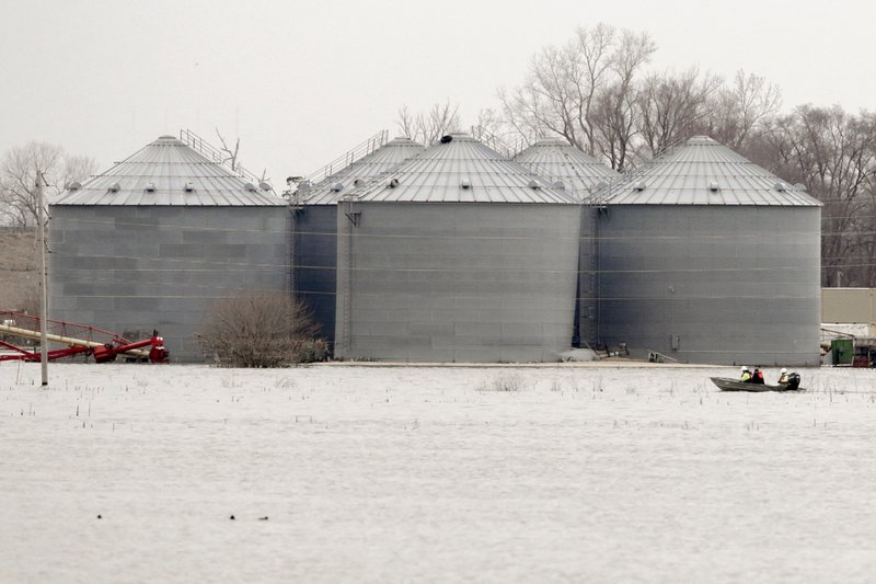 Utility workers travel by boat past grain bins in the flooded town of Pacific Junction, Iowa, Wednesday, April 3, 2019. (AP Photo/Nati Harnik)