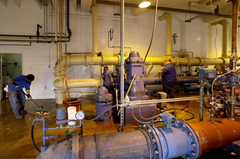 Employees clean the pump room at the Glenwood, Iowa, water plant Wednesday, April 3, 2019. Glenwood's wells and water-treatment plant were inundated by flood waters and are now being repaired and tested. (AP Photo/Nati Harnik)