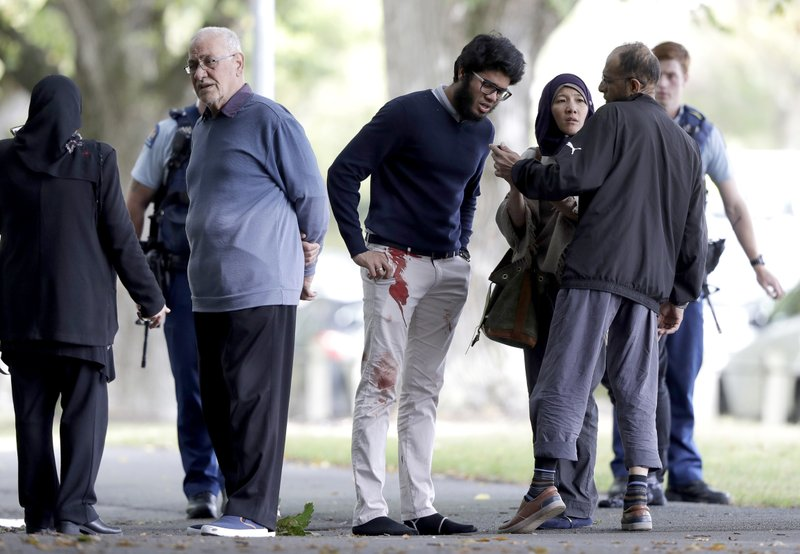 FILE - In this March 15, 2019, file photo, people stand across a road from a mosque following a shooting in central Christchurch, New Zealand. (AP Photo/Mark Baker, File)