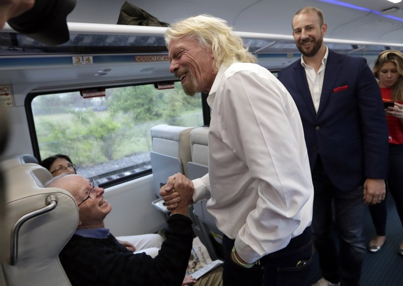 Richard Branson, of Virgin Group, center, greets a passenger while riding a Brightline train from Miami to West Palm Beach, Fla. (AP Photo/Lynne Sladky)