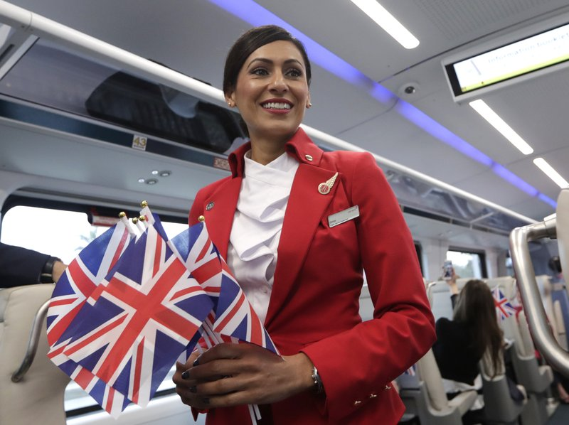 Ombi Farr passes out British flags while riding a Brightline train from Miami to West Palm Beach, Fla. (AP Photo/Lynne Sladky)
