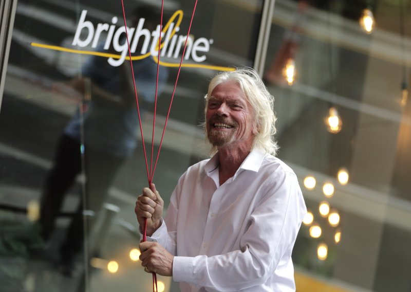 Richard Branson, of Virgin Group, prepares to unfurl a banner during a naming ceremony for the Brightline train station, to be renamed as Virgin MiamiCentral, Thursday, April 4, 2019, in Miami. (AP Photo/Lynne Sladky)
