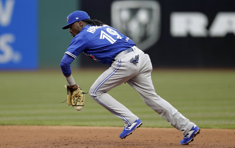 Toronto Blue Jays Alen Hanson bobbles the ball hit by Cleveland Indians' Tyler Naquin in the third inning of a baseball game, Thursday, April 4, 2019, in Cleveland. (AP Photo/Tony Dejak)