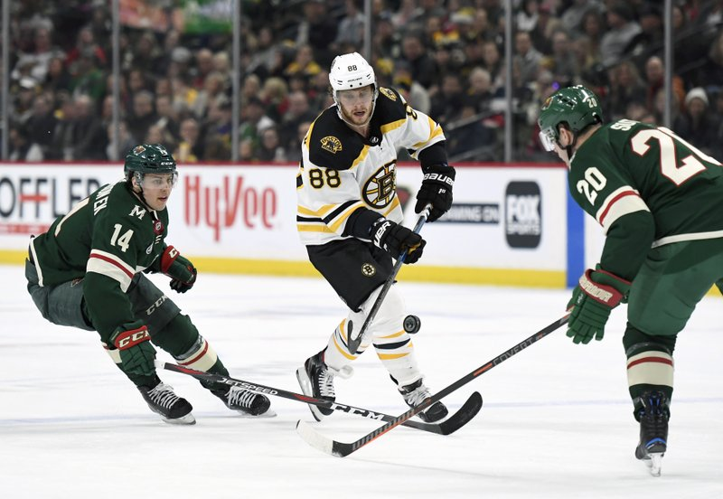 Boston Bruins' David Pastrnak (88), of the Czech Republic, passes away from Minnesota Wild's Joel Eriksson Ek (14), of Sweden, and Ryan Suter (20) during the second period of an NHL hockey game Thursday, April 4, 2019, in St. (AP Photo/Hannah Foslien)