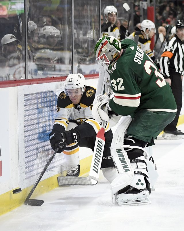 Boston Bruins' Karson Kuhlman (83) gets the puck past Minnesota Wild goaltender Alex Stalock (32) along the boards during the second period of an NHL hockey game Thursday, April 4, 2019, in St. (AP Photo/Hannah Foslien)