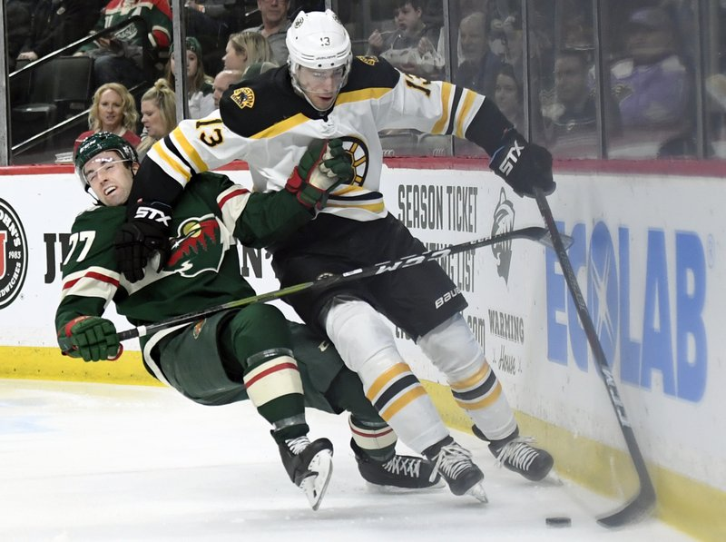 Boston Bruins' Charlie Coyle (13) has the puck against Minnesota Wild's Brad Hunt (77) during the second period of an NHL hockey game Thursday, April 4, 2019, in St. (AP Photo/Hannah Foslien)