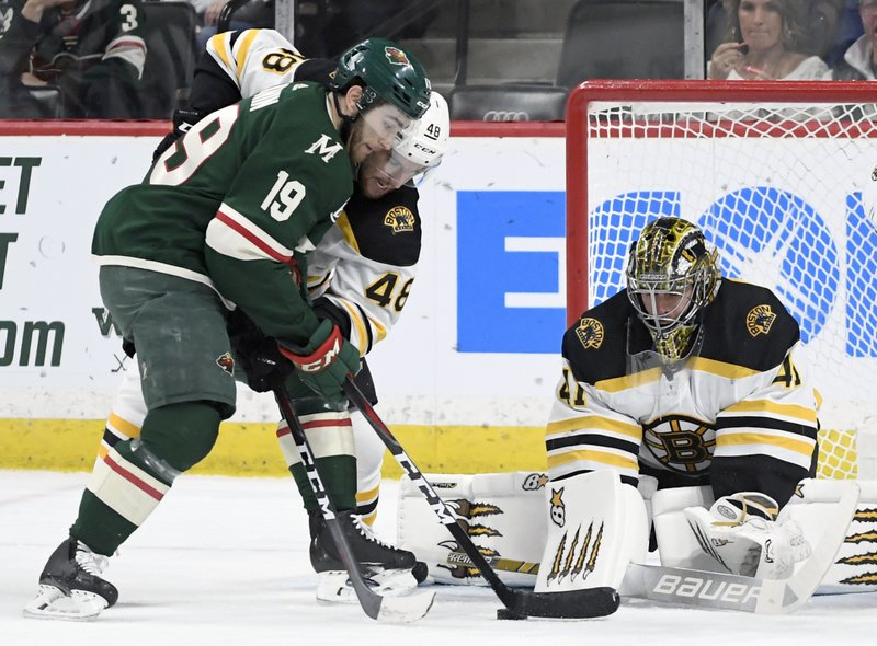 Boston Bruins' goaltender Jaroslav Halak (41), of Slovakia, stops a shot by Minnesota Wild's Luke Kunin (19) as Boston Bruins' Matt Grzelcyk (48) helps defend during the first period of an NHL hockey game Thursday, April 4, 2019, in St. (AP Photo/Hannah Foslien)