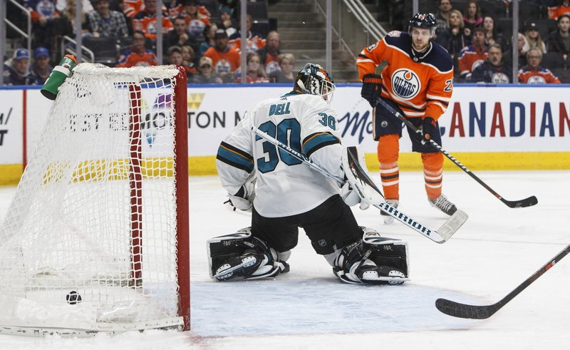 San Jose Sharks goalie Aaron Dell (30) gives up a goal to Edmonton Oilers' Leon Draisaitl (29) during the second period of an NHL hockey game Thursday, April 4, 2019, in Edmonton, Alberta. (Jason Franson/The Canadian Press via AP)