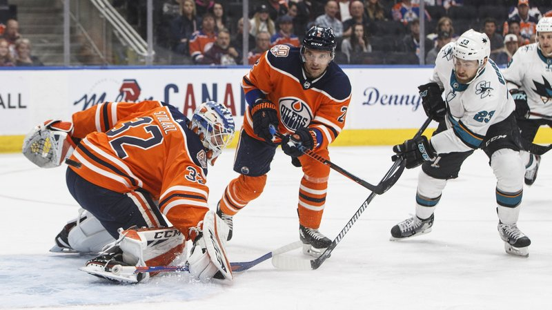 San Jose Sharks' Barclay Goodrow (23) is stopped by Edmonton Oilers goalie Anthony Stolarz (32) as Andrej Sekera (2) tries to defend during the first period of an NHL hockey game Thursday, April 4, 2019, in Edmonton, Alberta. (Jason Franson/The Canadian Press via AP)