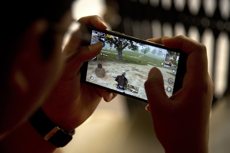 An Indian boy plays an online game PUBG on his mobile phone sitting outside his house  in Hyderabad, India, Friday, April 5, 2019. (AP Photo/ Mahesh Kumar A.)