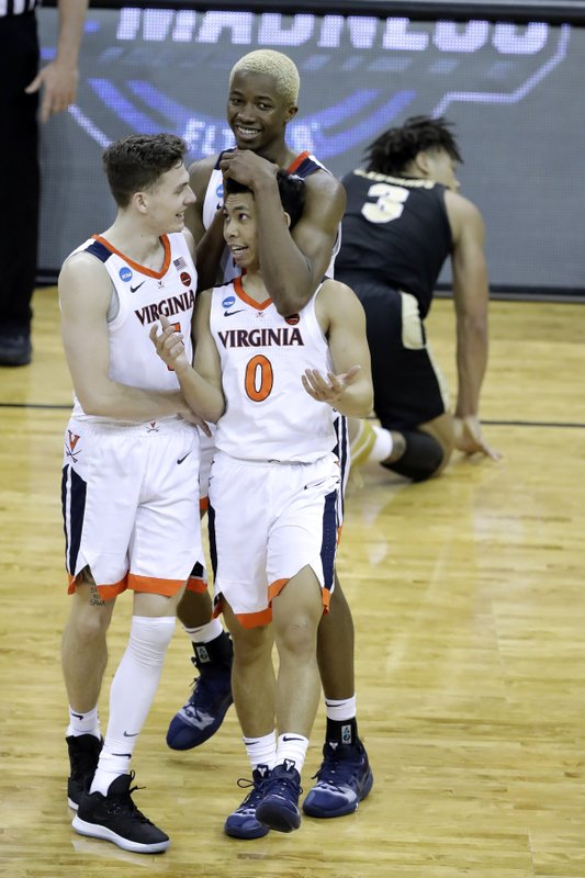 Virginia's Mamadi Diakite celebrates with teammates Kyle Guy, left, and Kihei Clark (0) as Purdue's Carsen Edwards (3) is seen in the background during overtime of the men's NCAA Tournament college basketball South Regional final game, Saturday, March 30, 2019, in Louisville, Ky. (AP Photo/Darron Cummings)