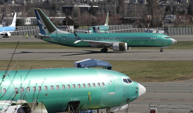 FILE- In this March 22, 2019, file photo a Boeing 737 Max 8 being built for Oman Air, top, taxis before takeoff from Renton Municipal Airport in Renton, Wash. (AP Photo/Ted S. Warren, File)