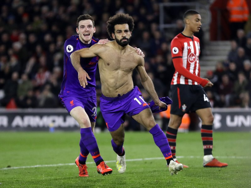 Liverpool's Mohamed Salah, center, celebrates with Andrew Robertson after scoring his side's second goal during the English Premier League soccer match between Southampton and Liverpool at St Mary's stadium in Southampton, England Friday, April 5, 2019. (AP Photo/Kirsty Wigglesworth)