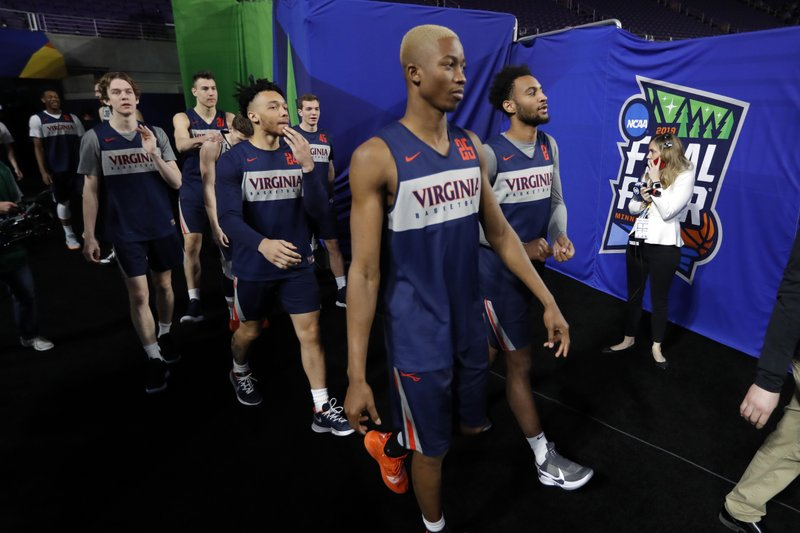Virginia players arrive for a practice session for the semifinals of the Final Four NCAA college basketball tournament, Friday, April 5, 2019, in Minneapolis. (AP Photo/Charlie Neibergall)