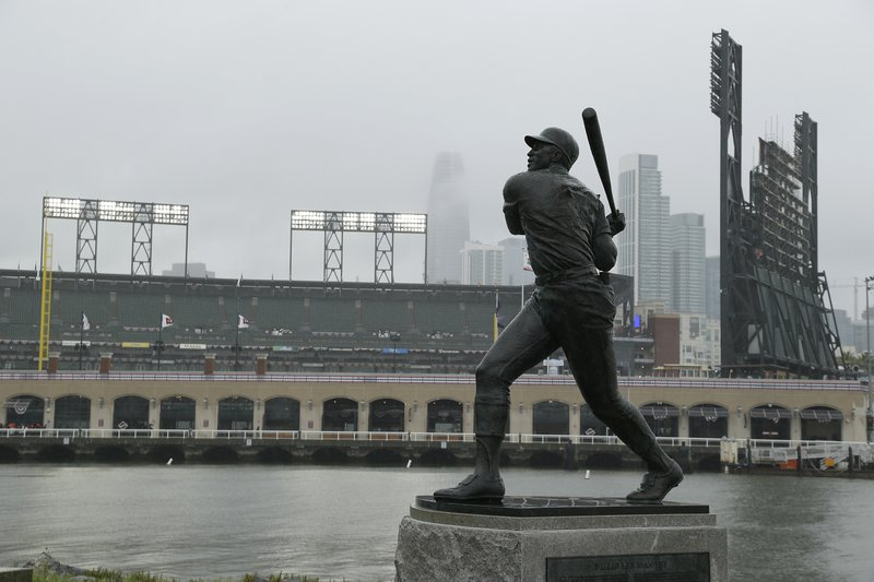 A statue of Hall of Famer Willie McCovey stands in the rain outside Oracle Park before the start of an opening day baseball game between the Tampa Bay Rays and San Francisco Giants Friday, April 5, 2019, in San Francisco. (AP Photo/Eric Risberg)