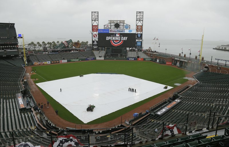 Groundskeepers clear water on the tarp-covered infield of Oracle Park before the start of an opening day baseball game between the Tampa Bay Rays and San Francisco Giants Friday, April 5, 2019, in San Francisco. (AP Photo/Eric Risberg)