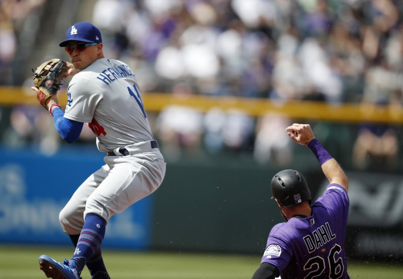 Los Angeles Dodgers second baseman Enrique Hernandez, left, throws to first base after putting out Colorado Rockies' David Dahl out at second base on the front end of a double play hit into by Nolan Arenado in the first inning of a baseball game Friday, April 5, 2019, in Denver. (AP Photo/David Zalubowski)